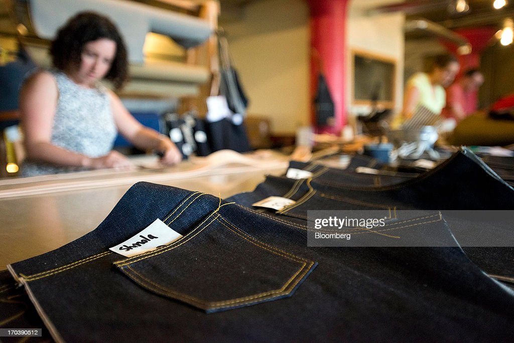 Employees create pairs of denim jeans at Detroit Denim, in Detroit, Michigan, U.S., on Wednesday, June 12, 2013. The Commerce Department is scheduled to release monthly business inventories data on June 13. Photographer: Ty Wright/Bloomberg via Getty Images