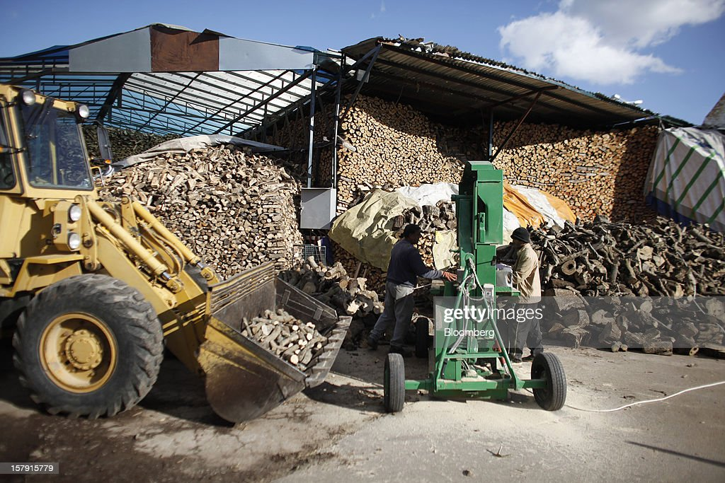 Employees cut logs to size using a bandsaw in the yard of a wood store in Athens, Greece, on Friday, Dec. 7, 2012. Greece, the epicenter of Europe's debt crisis since revealing a bloated spending gap in late 2009, has faced regular demands to get a firmer grip on the budget or risk being forced out of the euro. Photographer: Kostas Tsironis/Bloomberg via Getty Images