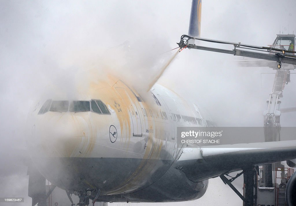 Employees de-ice an airplane by pouring a mix of water and alcohol over it at the Franz-Josef-Strauss airport in Munich, southern Germany, on January 21, 2013. In Munich, Germany's number two airport, some 161 flights -- or more than 15 percent -- were already cancelled due to the weather today.