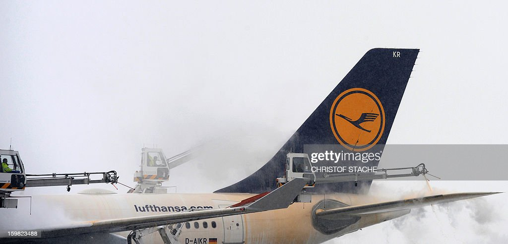 Employees de-ice an airplane by pouring a mix of water and alcohol of the Lufthansa jet during snowfall at the Franz-Josef-Strauss airport in Munich, southern Germany, on January 21, 2013. In Munich, Germany's number two airport, some 161 flights -- or more than 15 percent -- were already cancelled due to the weather today.