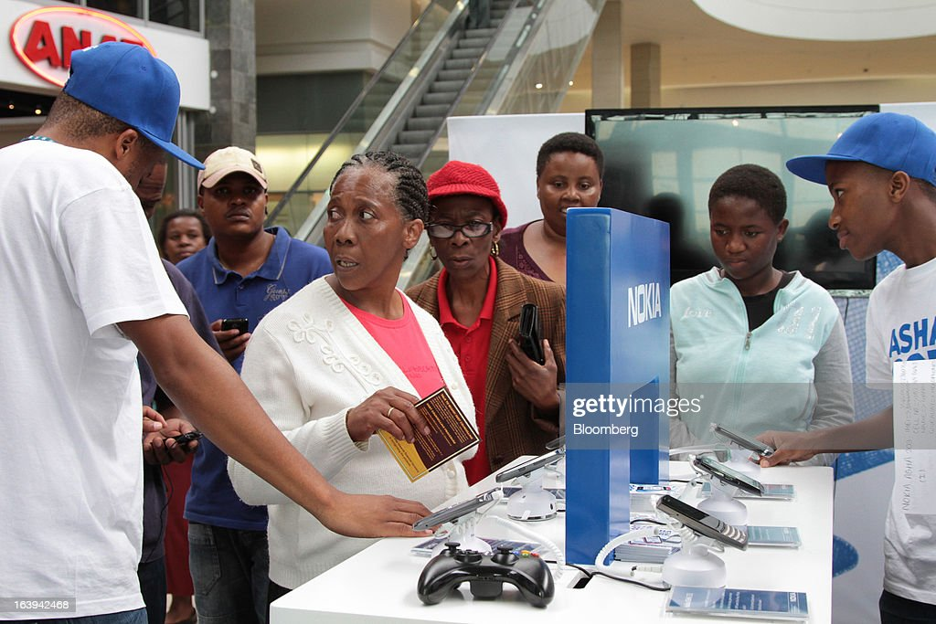 Employees demonstrate Nokia Asha smartphones to potential customers during a promotional 'activation day' event by Nokia Oyj in Maponya Mall in Soweto, South Africa, on Saturday, March 16, 2013. Nokia, based in Espoo, Finland, introduced three phones for its Asha line, sold primarily in emerging markets. Photographer: Nadine Hutton/Bloomberg via Getty Images