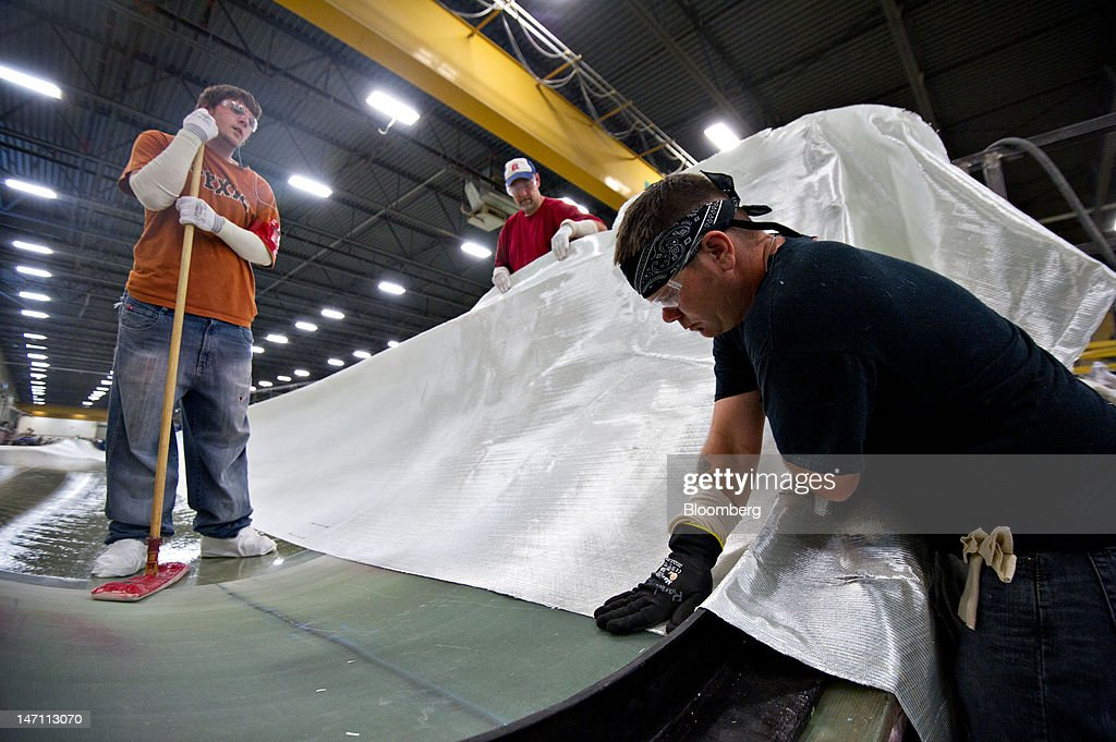 Employees Dillon Schultz, left, and Kyle Brow, center, watch as Randy Allen makes an adjustment to a layer of fiberglass fabric in a wind turbine blade mold made for General Electric Co.'s renewable energy business at TPI Composites Inc.'s manufacturing facility in Newton, Iowa, U.S., on Friday, June 22, 2012. The U.S. Census Bureau is scheduled to release durable goods data on June 27. Photographer: Daniel Acker/Bloomberg via Getty Images