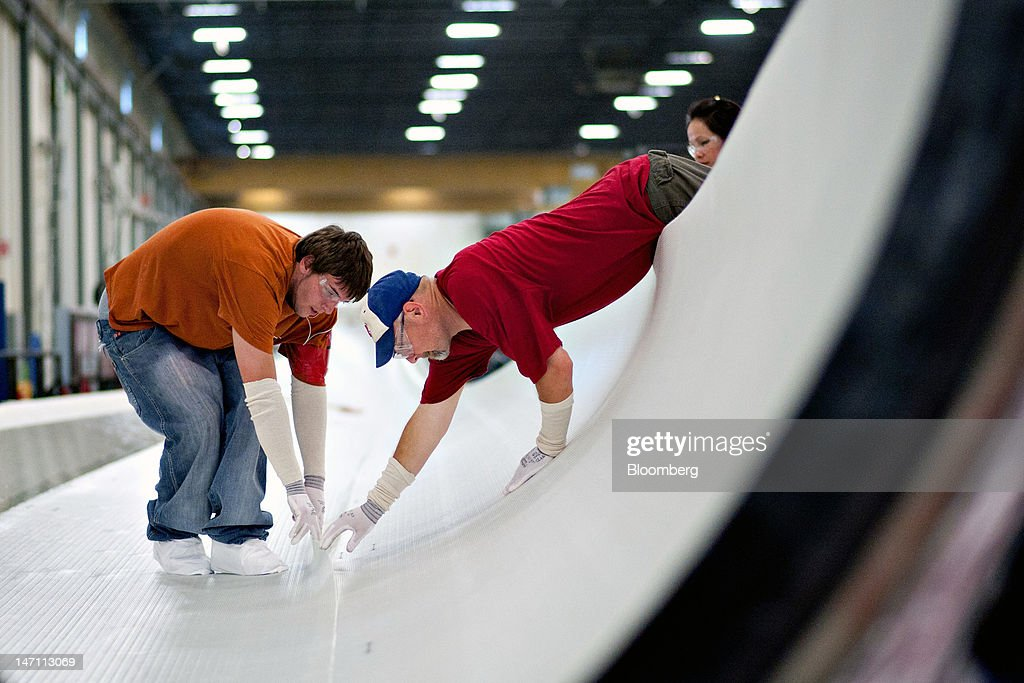 Employees Dillon Schultz, left, and Kyle Brown straighten a seam between layers of fiberglass fabric in a wind turbine blade mold made for General Electric Co.'s renewable energy business at TPI Composites Inc.'s manufacturing facility in Newton, Iowa, U.S., on Friday, June 22, 2012. The U.S. Census Bureau is scheduled to release durable goods data on June 27. Photographer: Daniel Acker/Bloomberg via Getty Images