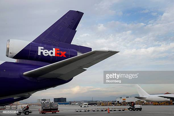 Employees drive carts on the tarmac past a cargo plane waiting to be loaded with shipments at the FedEx Corp distribution hub at Los Angeles...