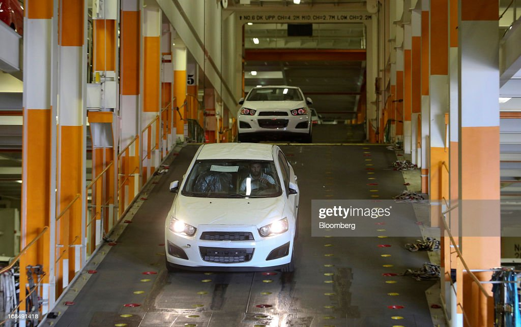 Employees drive new Chevrolet Sonic automobiles from the 'Silverstone Express' vehicle carrier during unloading at the port of Koper, operated by Luka Koper d.d., in Koper, Slovenia, on Thursday, May 9, 2013. The former Yugoslav nation, mired in its second recession since 2009, will contract this year and next, according to a May 3 report by the European Commission. Photographer: Chris Ratcliffe/Bloomberg via Getty Images