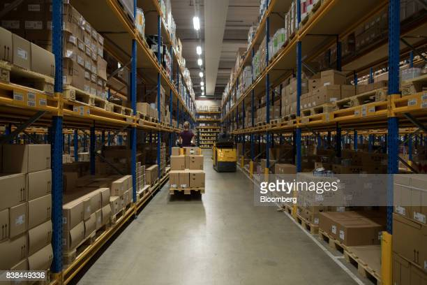 Employees drive pallet trucks between storage shelves inside the Akzo Nobel NV paint and coatings factory in Sassenheim Netherlands on Thursday Aug...