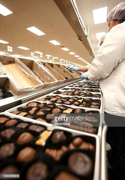 Employees fill boxes of chocolate on the production line of the See's Candies Inc packing facility in South San Francisco California US on Thursday...