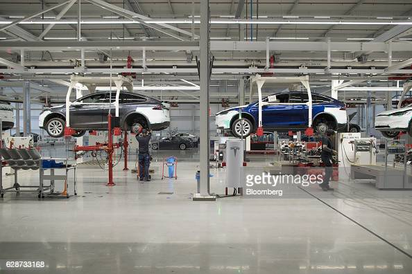 Employees fit rear axles to Tesla Model X sports utility vehicles as they sit in elevated cradles during assembly for the European market at the...