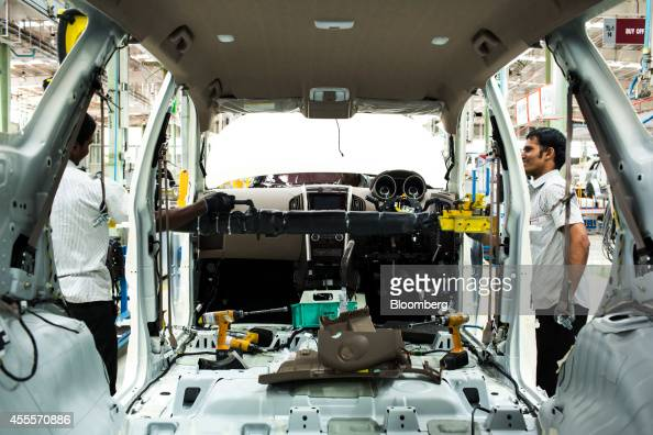 Employees fit the dashboard of a Mahindra Mahindra Ltd XUV 500 sportutility vehicle on the production line at the company's facility in Chakan...
