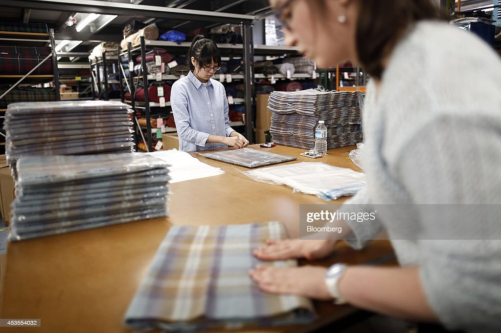 Employees fold and package tartan scarves following completion at Lochcarron John Buchan Ltd.'s production plant in Selkirk, U.K., on Tuesday, Aug. 12, 2014. Scottish nationalists seeking independence from the U.K. lost ground in the latest poll of voting intentions for the Sept. 18 referendum, as campaigners to keep the 307-year-old U.K. intact extended their lead. Photographer: Simon Dawson/Bloomberg via Getty Images