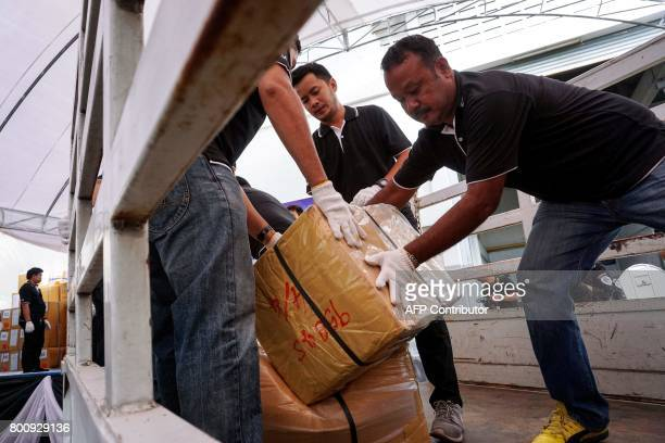 Employees from the Food and Drug Administration haul boxes of illegal substances from a truck before their incineration during the 47th Destruction...