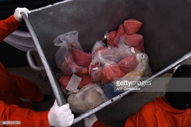 Employees from the Food and Drug Administration move bags of methamphetamines in a vat before their incineration during the 47th Destruction of...