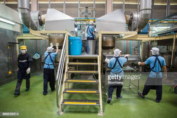 Employees fry garlic in a deepfrying machine at the Nithi Foods Co factory in the San Pa Tong district of Chiang Mai Thailand on Tuesday May 23 2017...