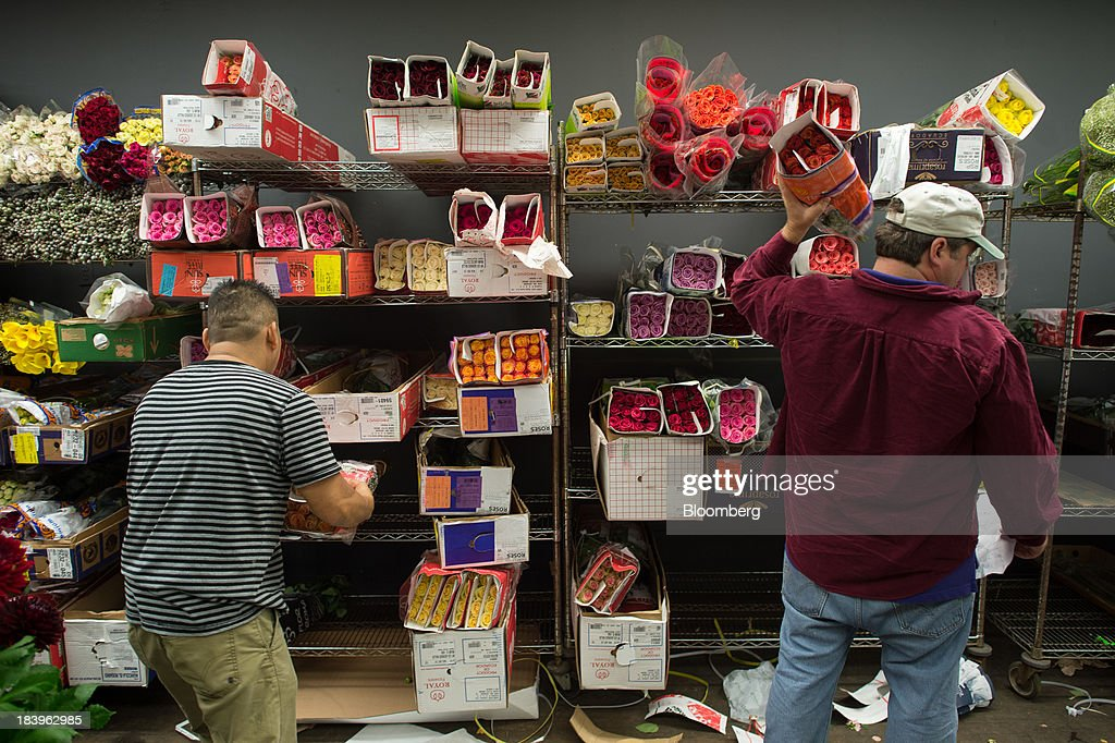 Employees gather flowers for orders at George Rallis Inc. wholesale flower shop in New York, U.S., on Monday, Oct. 7, 2013. Wholesale inventories figures, which were scheduled for Oct. 9 by the U.S. Census Bureau, will not be released due to the partial government shutdown. Photographer: Craig Warga/Bloomberg via Getty Images