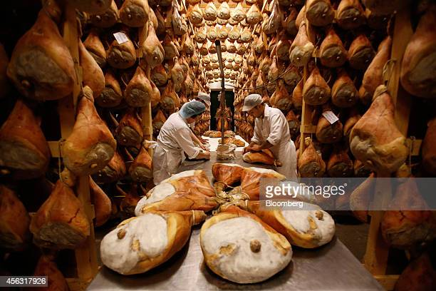 Employees grease hams with lard before hanging them to dry in storage as part of the Parma ham curing process at Pio Tosini Industria Prosciutti SpA...