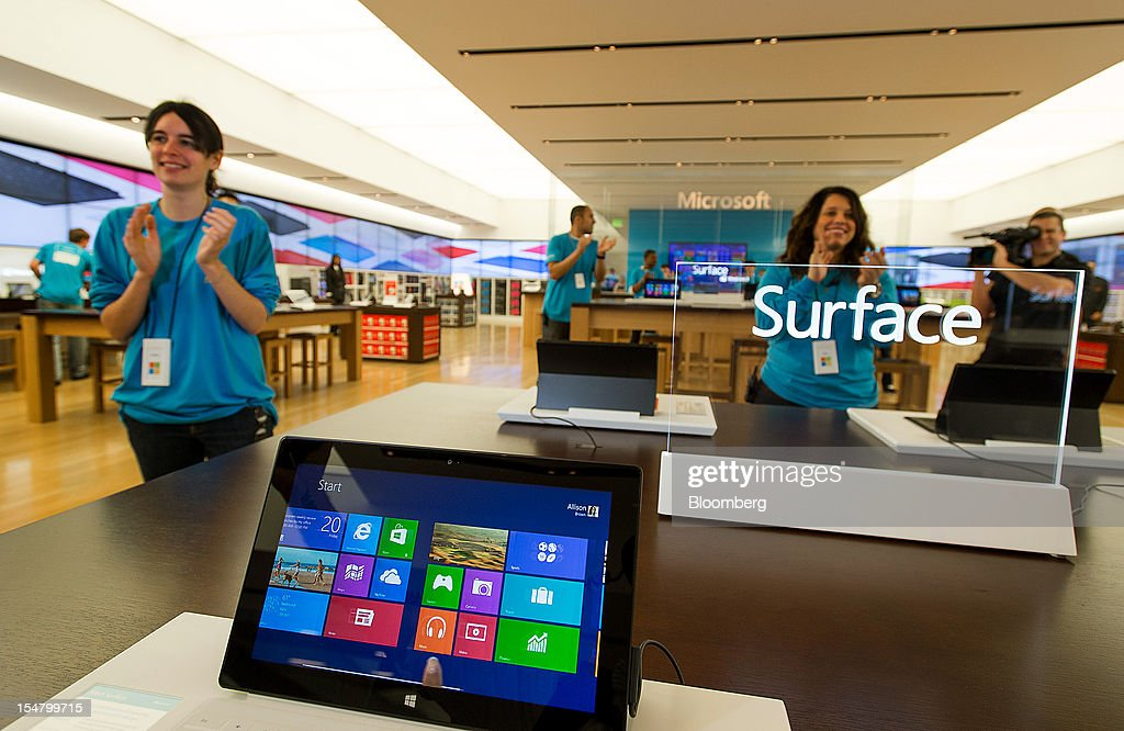 Employees greet customers at the opening of a Microsoft Corp. store in Bellevue, Washington, U.S., on Friday, Oct. 26, 2012. Microsoft Corp. introduced the biggest overhaul of its flagship Windows software in two decades, reflecting the rising stakes in its competition with Apple Inc. and Google Inc. for the loyalty of customers who are shunning personal computers and flocking to mobile devices. Photographer: Stuart Isett/Bloomberg via Getty Images