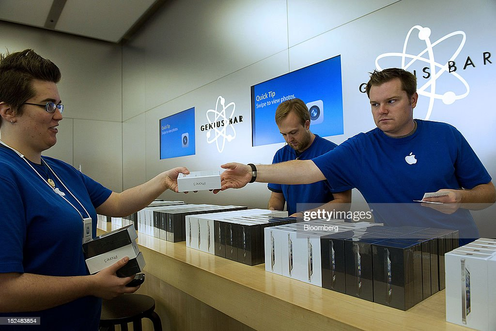 Employees hand off new Apple Inc. iPhone 5 devices at a store in San Francisco, California, U.S., on Friday, Sept. 21, 2012. Apple Inc. is poised for a record iPhone 5 debut and may not be able to keep up with demand as customers lined up in Sydney, Tokyo, Paris and New York to pick up the latest model of its top-selling product. Photographer: David Paul Morris/Bloomberg via Getty Images
