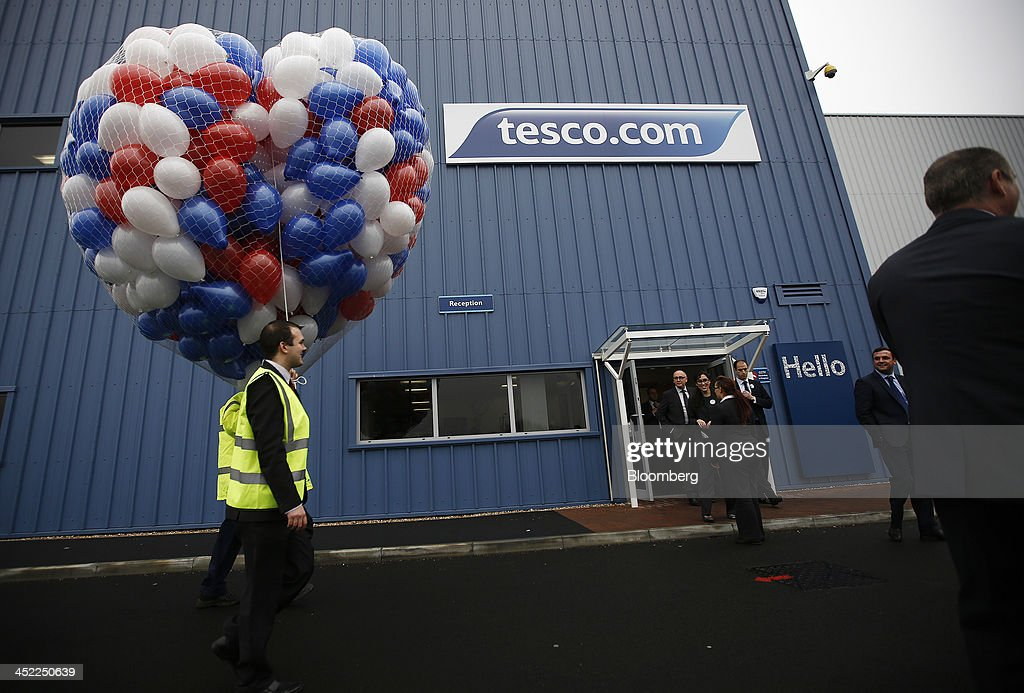 Employees hold a heart-shaped net of inflated balloons as they take part in a promotional event outside a Tesco Plc on-line distribution center, in Erith, U.K., on Wednesday, Nov. 27, 2013. Tesco Plc, the U.K.'s largest retailer, will sell land near some of its Polish hypermarkets to attract additional services around those stores. Photographer: Simon Dawson/Bloomberg via Getty Images