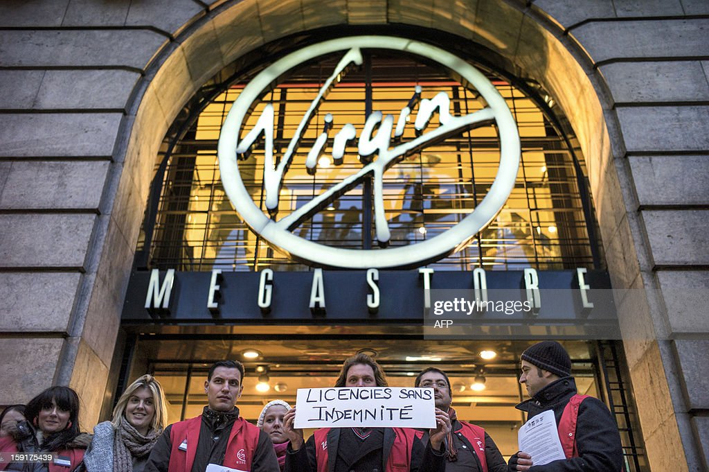 Employees hold a sign reading '' fired without compensation'' as they stand in front of a Virgin Megastore during a demonstration against planned job cuts at the entrance of the store on January 9, 2013 in Lyon. Virgin's Megastore music and book unit, which is known in France as a 'culture' retailer, said it will file for insolvency on January 9, 2013. Originally started by Richard Branson, the British billionaire and chairman of the Virgin Group, the Virgin Megastores were bought by the French Lagardere group in 2001.