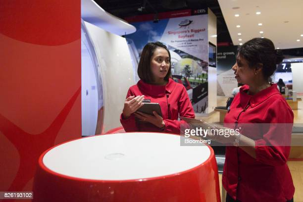 Employees hold Apple Inc iPads inside the DBS Group Holdings Ltd flagship bank branch in Singapore on Thursday Aug 3 2017 DBS Southeast Asia's...