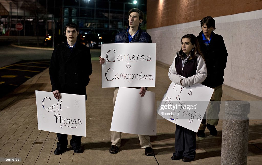 Employees hold signs for various types of merchandise as they prepare to organize shoppers waiting to enter a Best Buy Co. store prior to the store's midnight opening in Peoria, Illinois, U.S., on Thursday, Nov. 22, 2012. Discount store shoppers are prepared to wait in long lines on Black Friday, though they are skeptical about whether they'll get the best deals of the season. Photographer: Daniel Acker/Bloomberg via Getty Images