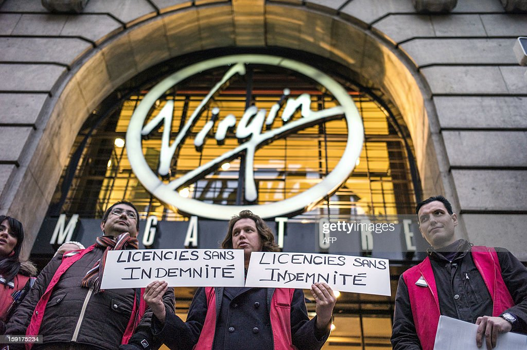 Employees hold signs reading '' fired without compensation'' as they stand in front of a Virgin Megastore during a demonstration against planned job cuts at the entrance of the store on January 9, 2013 in Lyon. Virgin's Megastore music and book unit, which is known in France as a 'culture' retailer, said it will file for insolvency on January 9, 2013. Originally started by Richard Branson, the British billionaire and chairman of the Virgin Group, the Virgin Megastores were bought by the French Lagardere group in 2001.