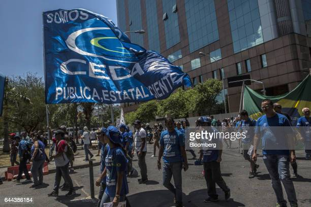 Employees hold up signs during a protest against the privatization of the State's water and sewage utility outside Cia Esadual de Aguas e Esgotos...