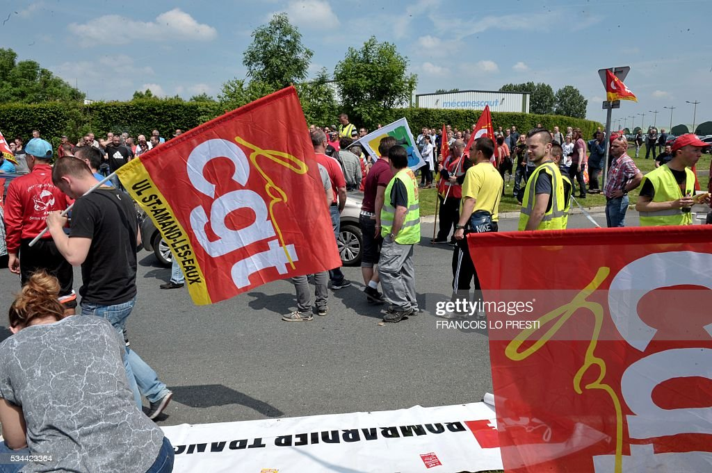 Employees holding French CGT union's flags block the access of the PSA plant on May 26, 2016 in Valenciennes, northern France during a protest against the government's labour market reforms. The French government's labour market proposals, which are designed to make it easier for companies to hire and fire, have sparked a series of nationwide protests and strikes over the past three months. / AFP / FRANCOIS
