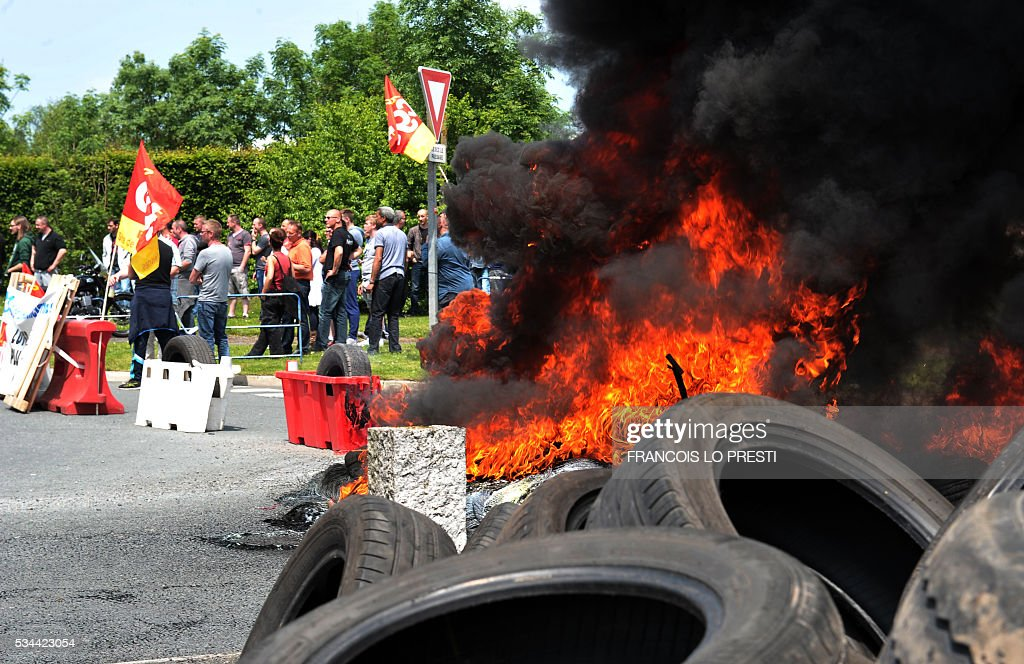 Employees holding French CGT union's flags stand next to a fire as they block the access of the PSA plant on May 26, 2016 in Valenciennes, northern France during a protest against the government's labour market reforms. The French government's labour market proposals, which are designed to make it easier for companies to hire and fire, have sparked a series of nationwide protests and strikes over the past three months. / AFP / FRANCOIS