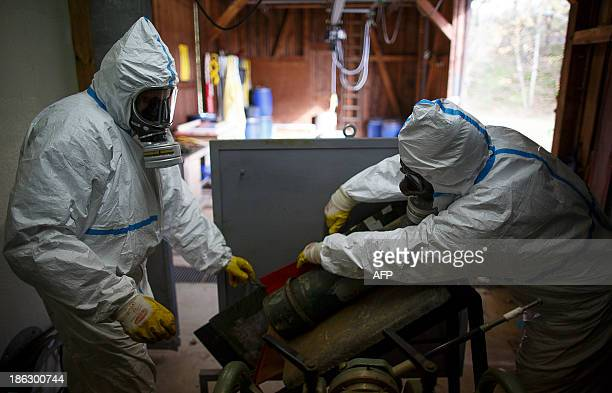 Employees in protective clothing prepare to xray a dummy grenade during a demonstration in a chemical weapons disposal facility at GEKA in Munster...