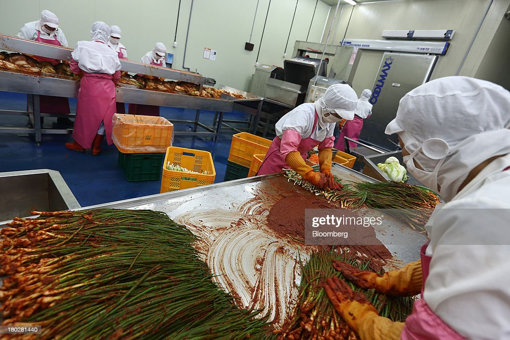 Employees in the foreground season scallion kimchi while employees in the back season kimchi on the production line at the Gamchilbaegi Co. kimchi factory in Gwangju, South Korea, on Tuesday, Sept. 10, 2013. Gross domestic product rose 1.1 percent in the second quarter from the preceding three months, the most in more than two years, central bank data showed Sept. 5. Photographer: SeongJoon Cho/Bloomberg via Getty Images