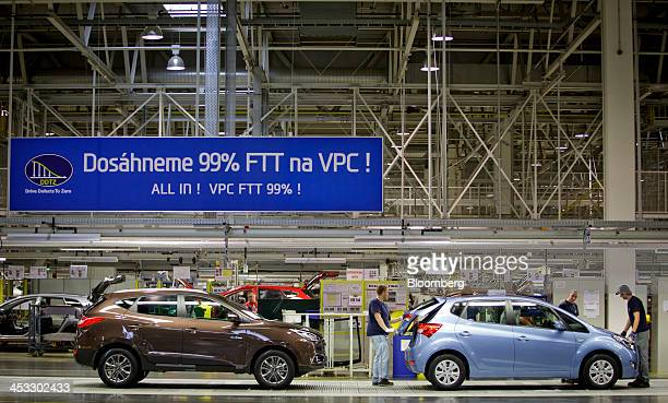 Employees inspect a Hyundai ix20 automobile right while an ix35 model stands behind at the end of the production line at the Hyundai Motor Co...