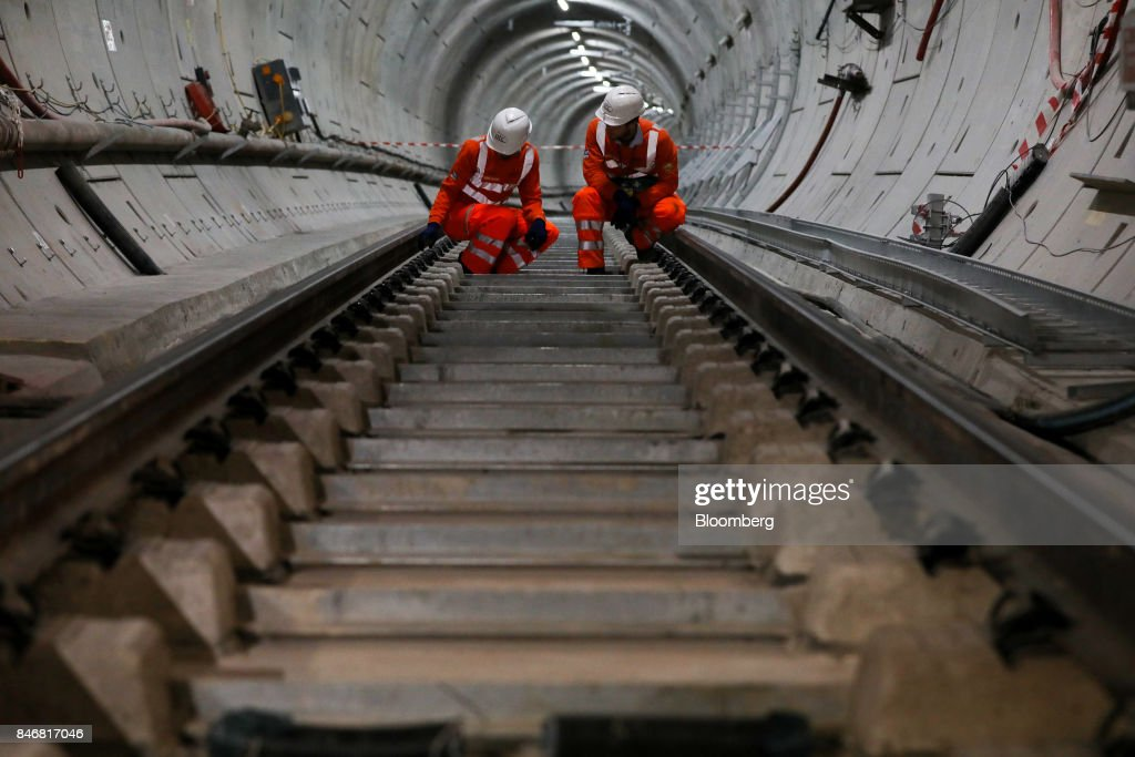 Employees inspect a section of Crossrail Ltd. track in a tunnel near Whitechapel station during an event to celebrate the completion of the permanent track on the Elizabeth line in London, U.K., on Thursday, Sept. 14, 2017. Crossrail, which will be known as the Elizabeth Line once its up and running, hasnt yet set fares, but transit agency Transport for London has indicated they will be significantly less than Heathrow Express with a charging structure more akin to the Tube. Photographer: Chris Ratcliffe/Bloomberg via Getty Images