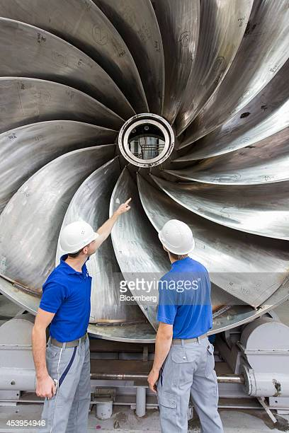 Employees inspect a Voith Francis hydropower turbine in the workshop at the Voith GmbH factory before shipping to the Cambambe ll power station in...