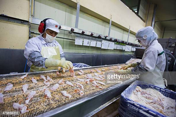 Employees inspect chicken tenders moving along a conveyor at the Harim Co factory in Iksan South Korea on Monday June 29 2015 Harim Group is a...