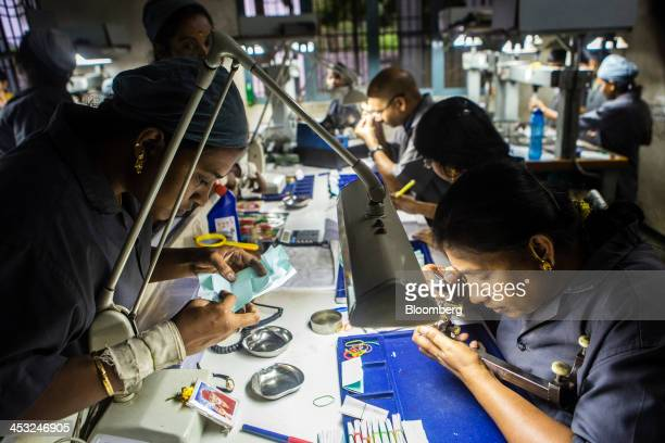Employees inspect cut and polished diamonds at the Viswa Devji Diamonds Pvt factory in Coimbatore Tamil Nadu India on Thursday Nov 28 2013 Indias...