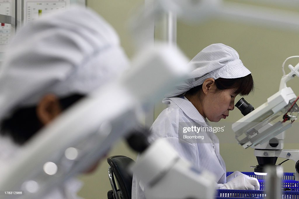 Employees inspect Flexible Printed Circuit Boards (F-PCB) through microscopes on the production line at the Seil Electronics Co. factory in Incheon, South Korea, on Wednesday, Aug. 28, 2013. South Korea has surpassed Brazil, Russia and India to become the second-biggest emerging stock market for the first time since 2006, as a stable won and record current-account surplus lure investors. Photographer: SeongJoon Cho/Bloomberg via Getty Images