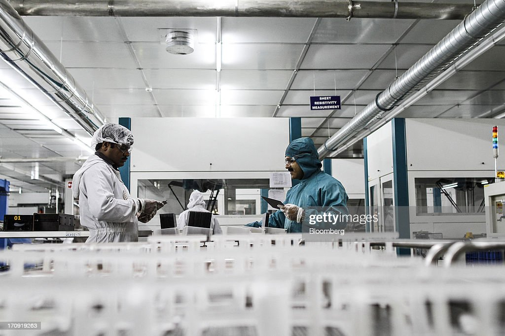 Employees inspect solar cells before loading into a diffusion furnace machine on the cell production line at the Tata Power Solar Systems Ltd. manufacturing plant in Bangalore, India, on Tuesday, June 11, 2013. Tata Groups solar unit is expanding its business building plants for customers, forecasting that offices and factories will be paying more for grid power than solar by 2016 in most Indian states. Photographer: Dhiraj Singh/Bloomberg via Getty Images