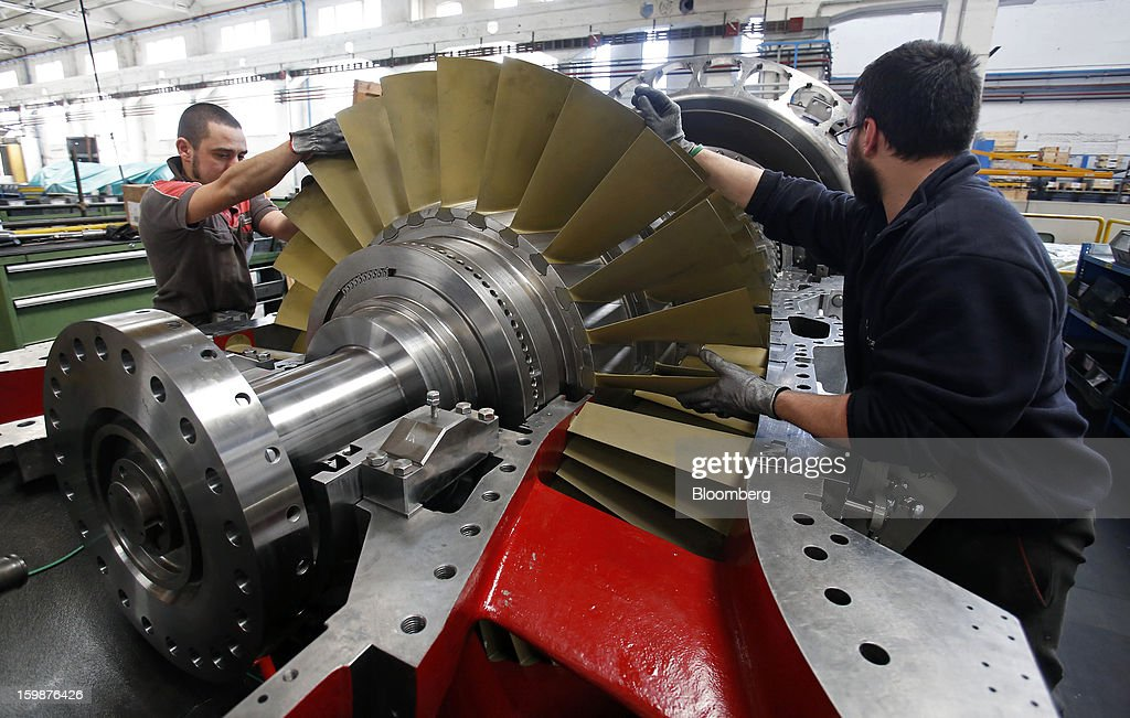 Employees inspect the blades on a gas turbine rotor assembly at Ansaldo Energia SpA's power-plant production facility in Genoa, Italy, on Friday, Jan. 18, 2013. Finmeccanica SpA is seeking binding bids for assets, including a majority stake in Ansaldo Energia, by Jan. 23, while a final decision will be made at a later board meeting, Ansa reported Jan. 16. Photographer: Alessia Pierdomenico/Bloomberg via Getty Images