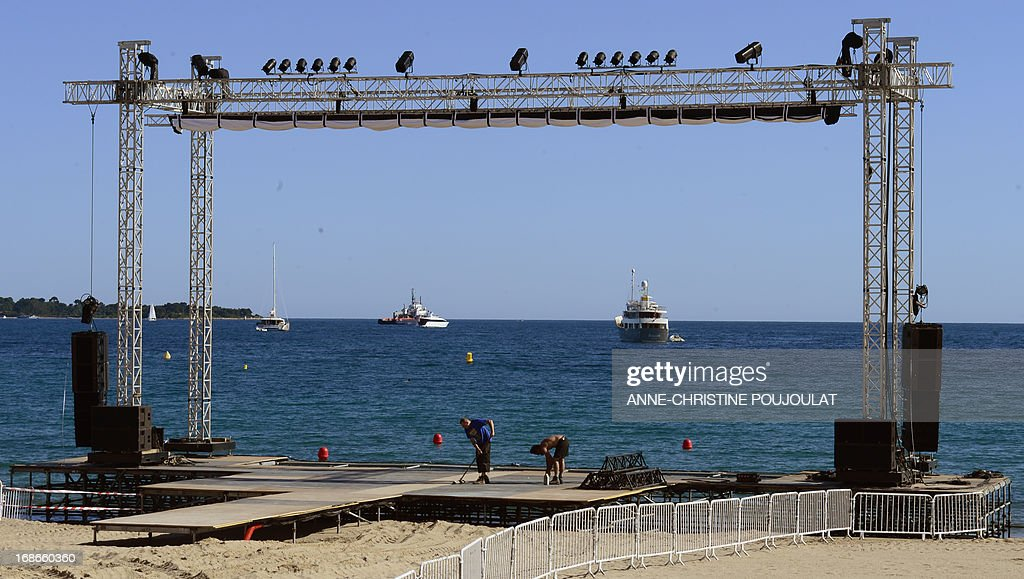 Employees install a giant screen on May 13, 2013 on the beach in Cannes, two days before the opening of the 66th Cannes Film Festival.