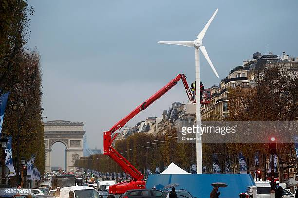 Employees install a wind turbine to provide electricity for Christmas illuminations on the ChampsElysee on November 25 2015 in Paris France This...