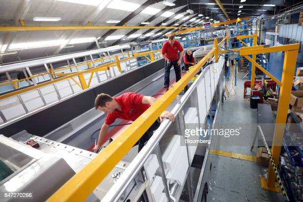 Employees install components to the upper deck of an Enviro 400 bus at the Alexander Dennis Ltd factory in Scarborough UK on Wednesday Sept 13 2017...