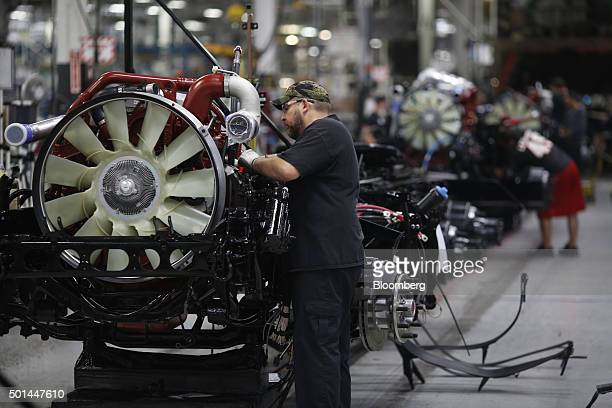 Employees install engines onto truck chassis at the Mack Truck Inc cab and vehicle assembly plant in Macungie Pennsylvania US on Thursday Dec 10 2015...