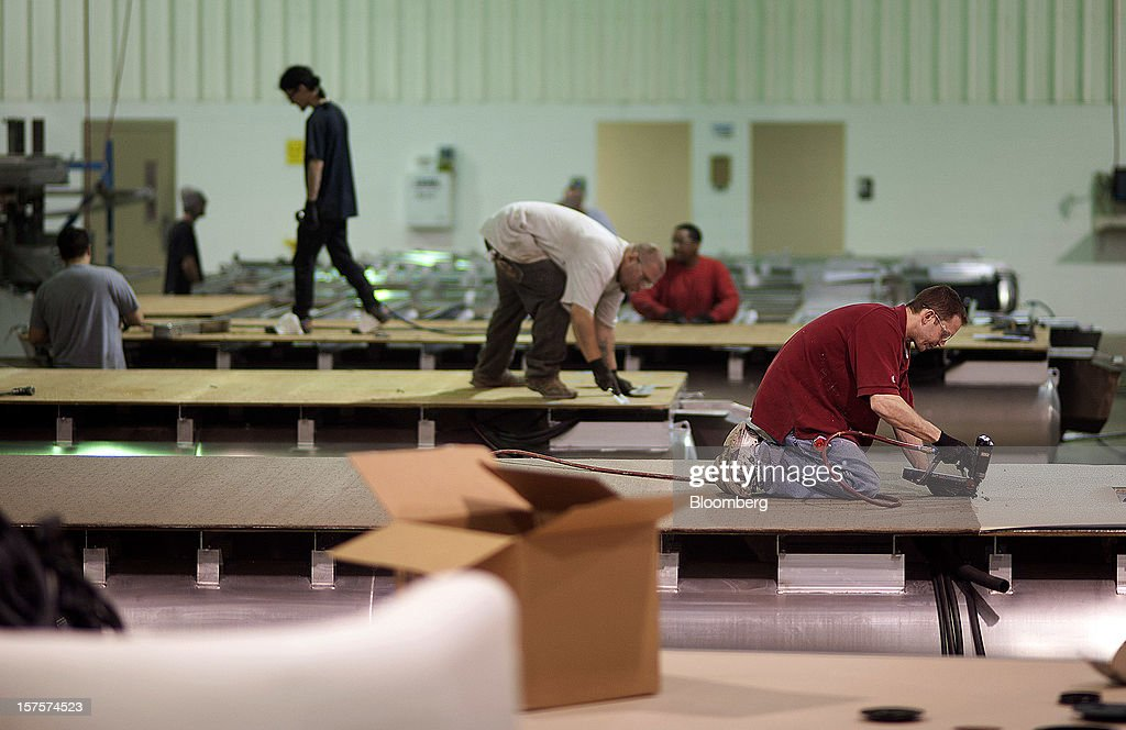 Employees install flooring on the main deck of pontoon boats on the assembly line at the Nautic Global Group production facility in Elkhart, Indiana, U.S., on Tuesday, Dec 4, 2012. The U.S. Census Bureau is scheduled to release factory orders data on Dec. 5. Photographer: Ty Wright/Bloomberg via Getty Images