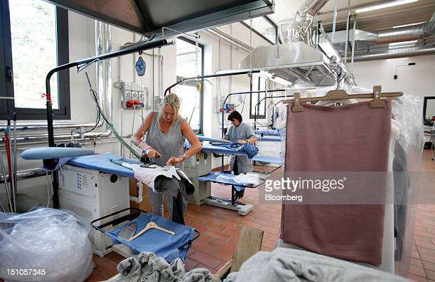 Employees iron garments during the manufacturing of garments at the Brunello Cucinelli SpA production facility in Solomeo near Perugia Italy on...