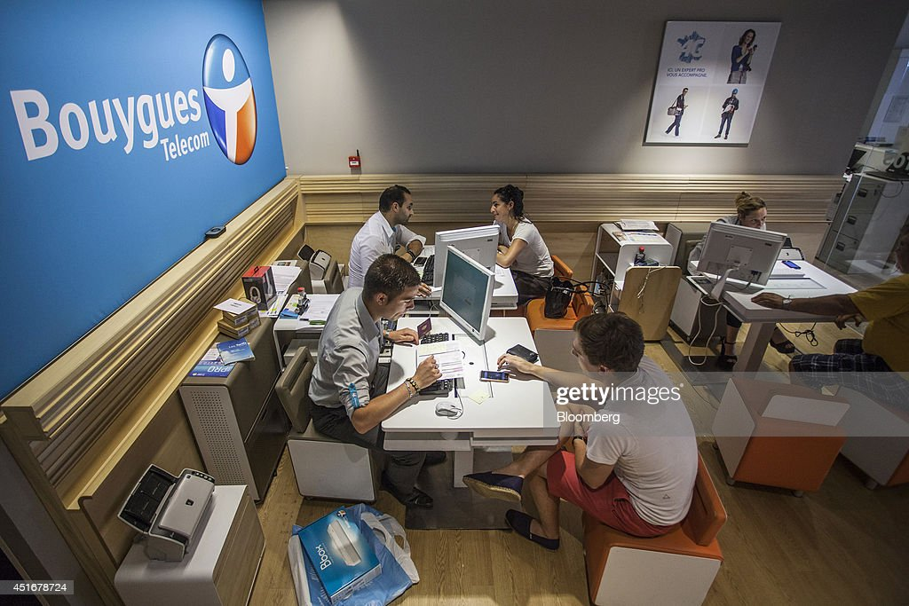 Employees, left, speak with customers, right, as they sit inside a Bouygues Telecom store, operated by Bouygues SA in Paris, France, on Thursday, July 3, 2014. Bouygues Telecom, France's third-largest mobile operator, was looking for a buyer as profitability and cash generation declined. Photographer: Balint Porneczi/Bloomberg via Getty Images