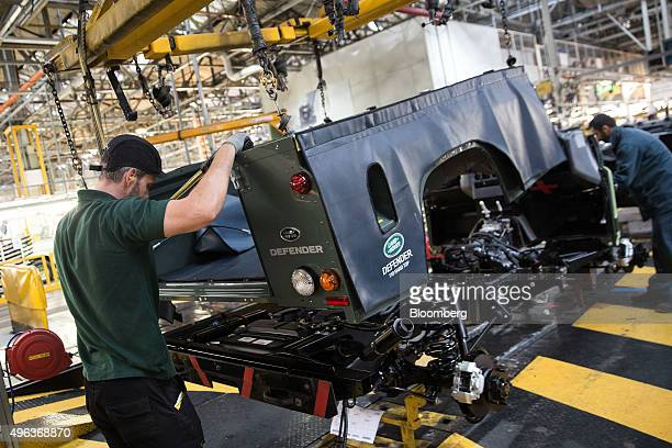 Employees lift the rear outer shell onto a chassis of a Land Rover Defender automobile at Tata Motors Ltd's Jaguar Land Rover vehicle manufacturing...