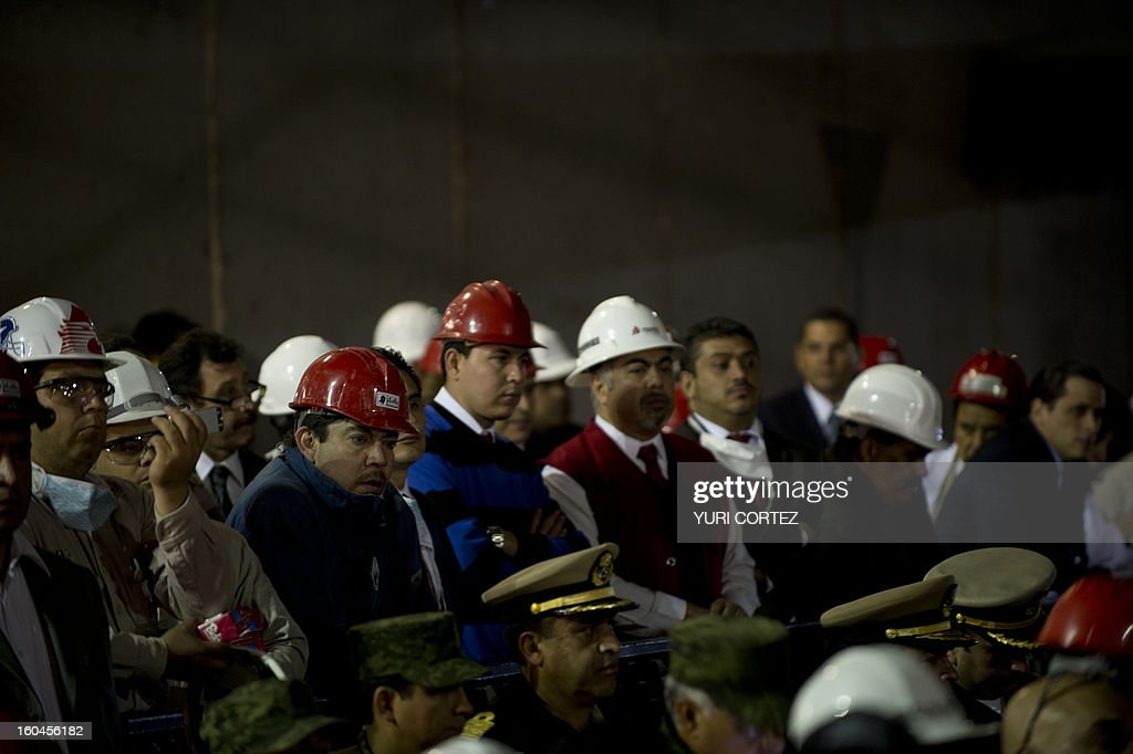 Employees listen as the Minister of the Interior, Miguel Angel Osorio Chong (out of frame) addresses a press conference at the headquarters of state-owned Mexican oil giant Pemex in Mexico City on January 31, 2013, following a blast inside the building. An explosion rocked the skyscraper, leaving up to 25 dead and 101 injured, as a plume of black smoke billowed from the 54-floor tower, according to official sources. AFP PHOTO / YURI CORTEZ