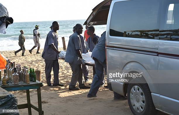 Employees load a body into a van after heavilyarmed gunmen opened fire in the Ivory Coast resort town of GrandBassam leaving bodies strewn on the...