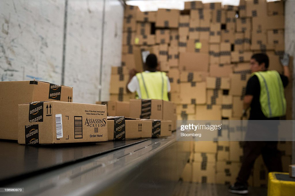 Employees load a truck with boxes to be shipped at the Amazon.com Inc. distribution center in Phoenix, Arizona, U.S. on Monday, Nov. 26, 2012. U.S. retailers are extending deals into Cyber Monday and beyond to try to sustain a 13 percent gain in Thanksgiving weekend sales. Photographer: David Paul Morris/Bloomberg via Getty Images